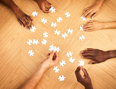 Buy stock photo Cropped shot of a group of businesspeople completing a puzzle together on a table