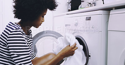 Buy stock photo Shot of a focused young woman putting in clothes in the washing machine to get washed at home during the day