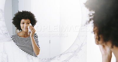 Buy stock photo Shot of a confident young woman wiping her face with a cleanser while looking into a mirror in the bathroom at home during the day