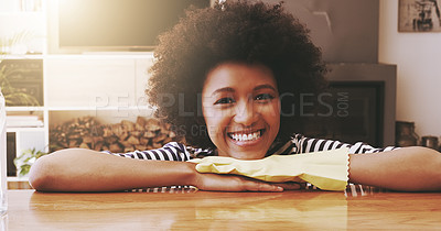 Buy stock photo Portrait of a cheerful young woman resting with her hands on a table while wearing yellow cleaning gloves at home during the day