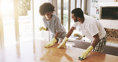 Buy stock photo Shot of a cheerful young couple cleaning the surface of a table with cleaning equipment together at home