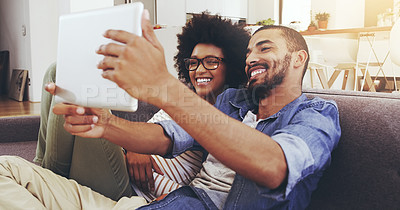 Buy stock photo Shot of a cheerful young couple seated on a couch while taking a self portrait with a digital tablet in the living room at home