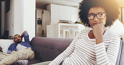 Buy stock photo Shot of a annoyed looking woman seated on a couch resting with her chin on her fist while ignoring her boyfriend at home