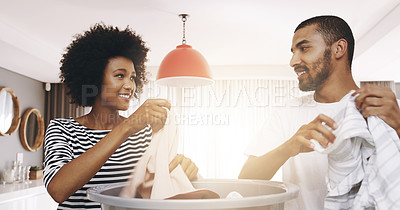 Buy stock photo Shot of a cheerful young couple working together and sorting out washing at home during the day