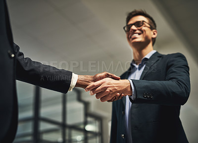 Buy stock photo Low angle shot of two businessmen shaking hands in an office