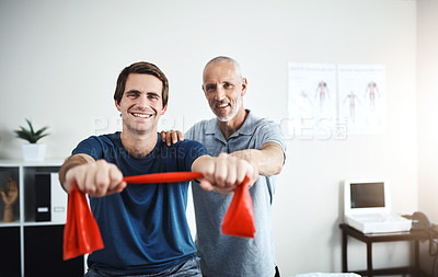 Buy stock photo Portrait of a physiotherapist helping a patient stretch with resistance bands