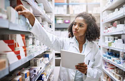 Buy stock photo Cropped shot of an attractive young female pharmacist working in a pharmacy