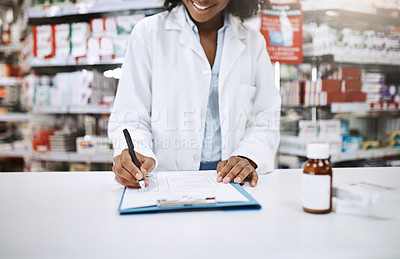 Buy stock photo Cropped shot of an unrecognizable young female pharmacist working in a pharmacy