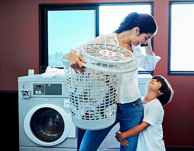 Buy stock photo Cropped shot of a young attractive mother doing laundry with her son at home