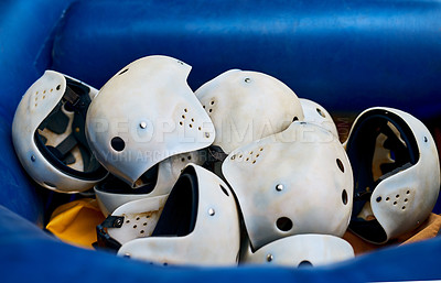 Buy stock photo Closeup of a pile of protective helmets lying inside of a rubber boat outside during the day