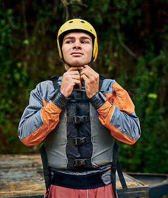 Buy stock photo Shot of a determined young man putting on a protective helmet and getting ready to go river rafting outside during the day
