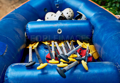 Buy stock photo Shot of a a bunch of river rafting equipment lying on top of each other inside of a rubber bout outside during the day