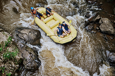 Buy stock photo High angle shot of a group of determined young men on a rubber boat busy paddling on strong river rapids outside during the day