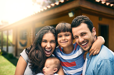 Buy stock photo Cropped portrait of a happy young family of four outside with their house in the background