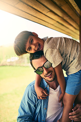 Buy stock photo Cropped portrait of a happy young father and son outside in their yard