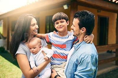 Buy stock photo Cropped shot of a happy young family of four outside with their house in the background