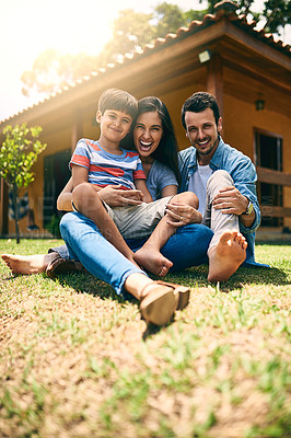 Buy stock photo Full length portrait of a happy young family of three sitting on their lawn in the backyard