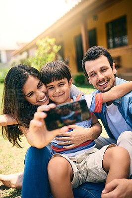 Buy stock photo Cropped shot of a happy young family of three taking selfies white sitting in the backyard