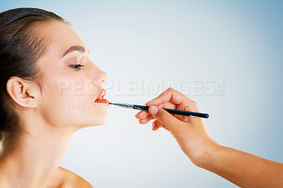 Buy stock photo Cropped studio shot of a hand applying lipstick to beautiful young woman with a brush against a blue background