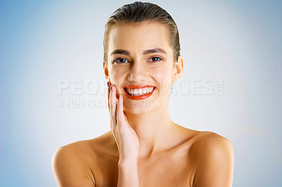 Buy stock photo Studio portrait of a beautiful young woman feeling her skin against a blue background