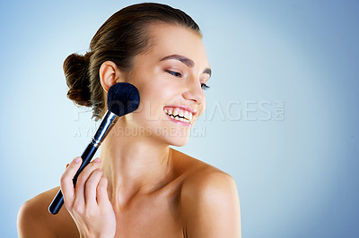 Buy stock photo Studio shot of a beautiful young woman applying makeup with a brush against a blue background