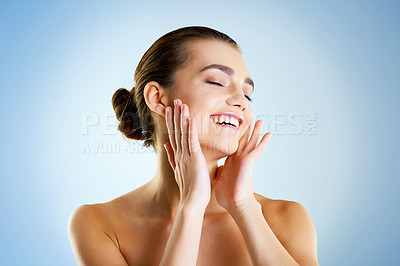 Buy stock photo Studio shot of a beautiful young woman feeling her skin against a blue background