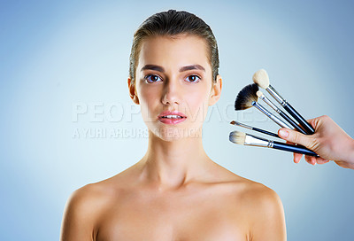 Buy stock photo Studio portrait of a hand holding makeup brushes next to a beautiful young woman against a blue background