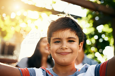 Buy stock photo Portrait of an adorable little boy taking a selfie with his parents in the background