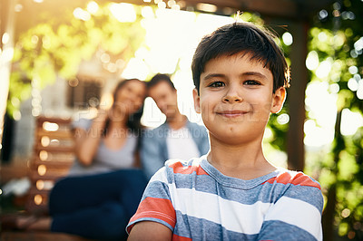 Buy stock photo Portrait of an adorable little boy standing outside with his parents in the background