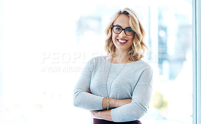 Buy stock photo Portrait of an attractive young businesswoman standing with her arms crossed in an office
