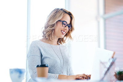Buy stock photo Shot of an attractive young businesswoman working on a laptop in an office
