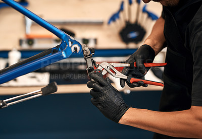 Buy stock photo Cropped shot of a man repairing a bicycle in a workshop