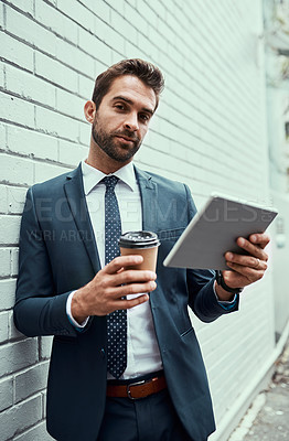 Buy stock photo Portrait of a handsome young businessman using a digital tablet outdoors