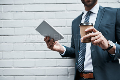 Buy stock photo Closeup shot of an unidentifiable businessman using a digital tablet outdoors