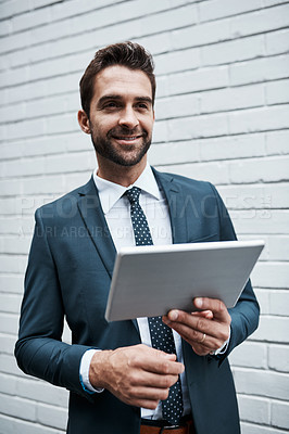 Buy stock photo Shot of a handsome young businessman using a digital tablet outdoors