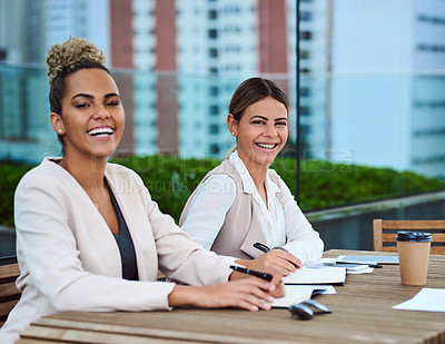 Buy stock photo Cropped portrait of two attractive young businesswomen sitting in the boardroom during a meeting
