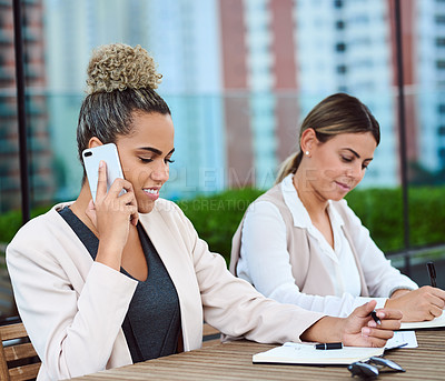 Buy stock photo Cropped shot of an attractive young businesswoman using her cellphone during a meeting in the boardroom