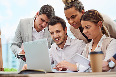 Buy stock photo Cropped shot of a group of businesspeople gathered around a laptop during a meeting in the boardroom