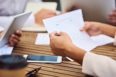 Buy stock photo Cropped shot of an unrecognizable young businesswoman reading paperwork during a meeting in the boardroom