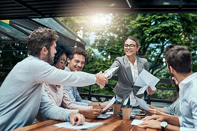 Buy stock photo Shot of businesspeople shaking hands during a meeting at a cafe