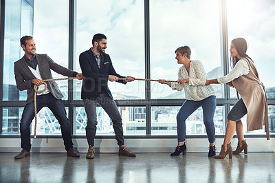 Buy stock photo Shot of a group of businesspeople pulling on a rope during tug of war in an office