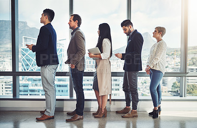 Buy stock photo Shot of a group of businesspeople standing in line in an office