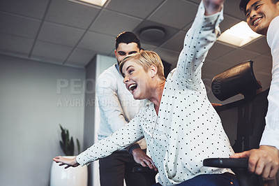 Buy stock photo Shot of businesspeople having fun by taking their colleague for a ride in her chair in the office
