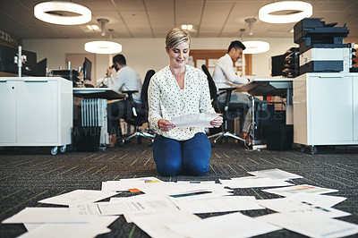 Buy stock photo Shot of a businesswoman working with paperwork on the floor in the office