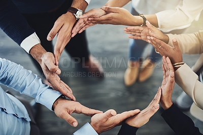 Buy stock photo High angle shot of a group of unidentifiable businesspeople forming a circle with their hands