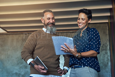 Buy stock photo Cropped shot of two creative businesspeople looking over some paperwork in the office