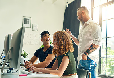 Buy stock photo Shot of two young creative businesspeople working on a computer in their office under the guidance of their manager