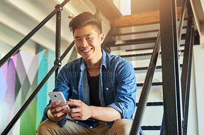 Buy stock photo Cropped portrait of a handsome young male designer sending a text message in the office