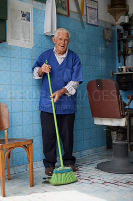 Buy stock photo Shot of a senior man working in his barber shop