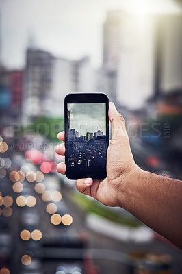 Buy stock photo Cropped shot of an unrecognizable man taking a picture with a cellphone in the city